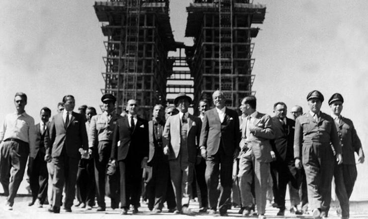 <strong> De chapéu, o presidente Juscelino caminha</strong> com assessores e correligionários nas obras da futura capital, tendo ao fundo as torres do Congresso Nacional. Brasília, 1959
