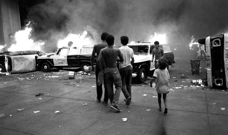 <strong> Viaturas da polícia incendiadas </strong> em protesto em Brasília contra o Plano Cruzado 2; os manifestantes faziam passeata e reagiram à forte repressão policial