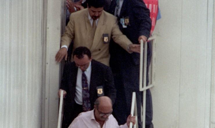 <strong> O empresário Paulo César Farias </strong> (de camisa cor de rosa) desembarcaem São Paulo acompanhado por agentes da Polícia Federal, vindo da Tailândia