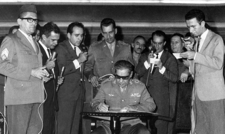 <strong> Arthur da Costa e Silva, </strong> representante do Exército no Comando Supremo da Revolução, assina o Ato Institucional da ditadura, primeiro de uma série de decretos autoritários