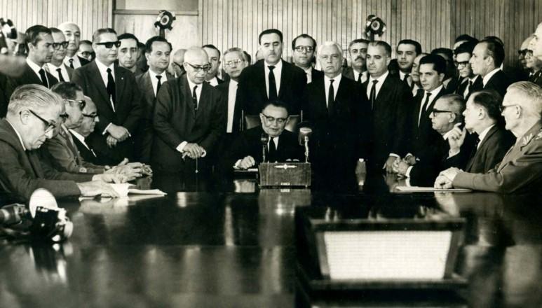 <strong> Castelo Branco,</strong> ao centro, assina o Ato Institucional n&ordm; 2, em Bras&iacute;lia. Aparecem na foto os dois futuros generais presidentes Costa e Silva (2&ordm; sentado &agrave; esq.) e Ernesto Geisel (sentado &agrave; dir., em primeiro plano)