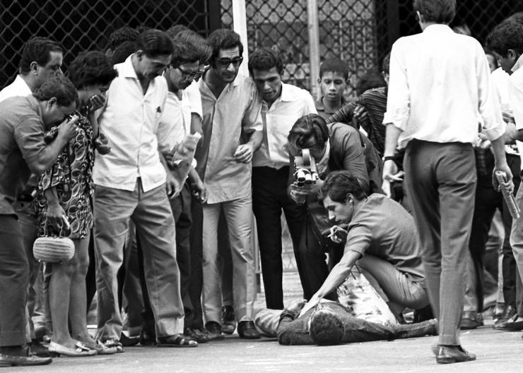 <strong> Baleado pela repressão,</strong> jovem &eacute; cercado por manifestantes e populares