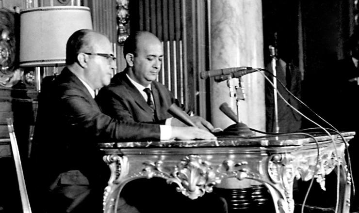 <strong> Gama e Silva </strong> (à esq.), ministro da Justiça, anuncia a decretação do Ato Institucional n° 5 em rede nacional  <br />