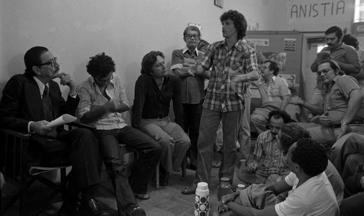<strong> Teot&ocirc;nio Vilela (&agrave; esq.) e Marcos Freire </strong> (sentado, de camisa escura)&nbsp;visitam os presos pol&iacute;ticos de Itamarac&aacute; (PE), em 19 de julho de 1979