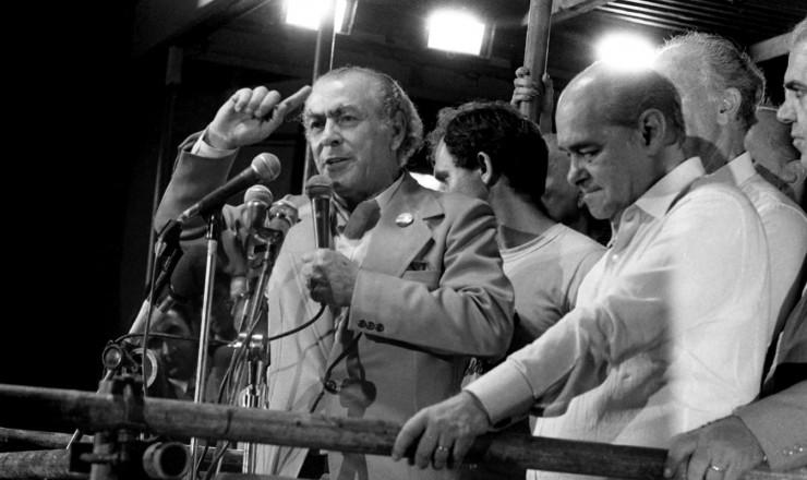 <strong> O governador Leonel Brizola </strong> discursa na Candel&aacute;ria ao lado de Tancredo Neves (MG, &agrave; sua dir.) e Jos&eacute; Richa (PR)